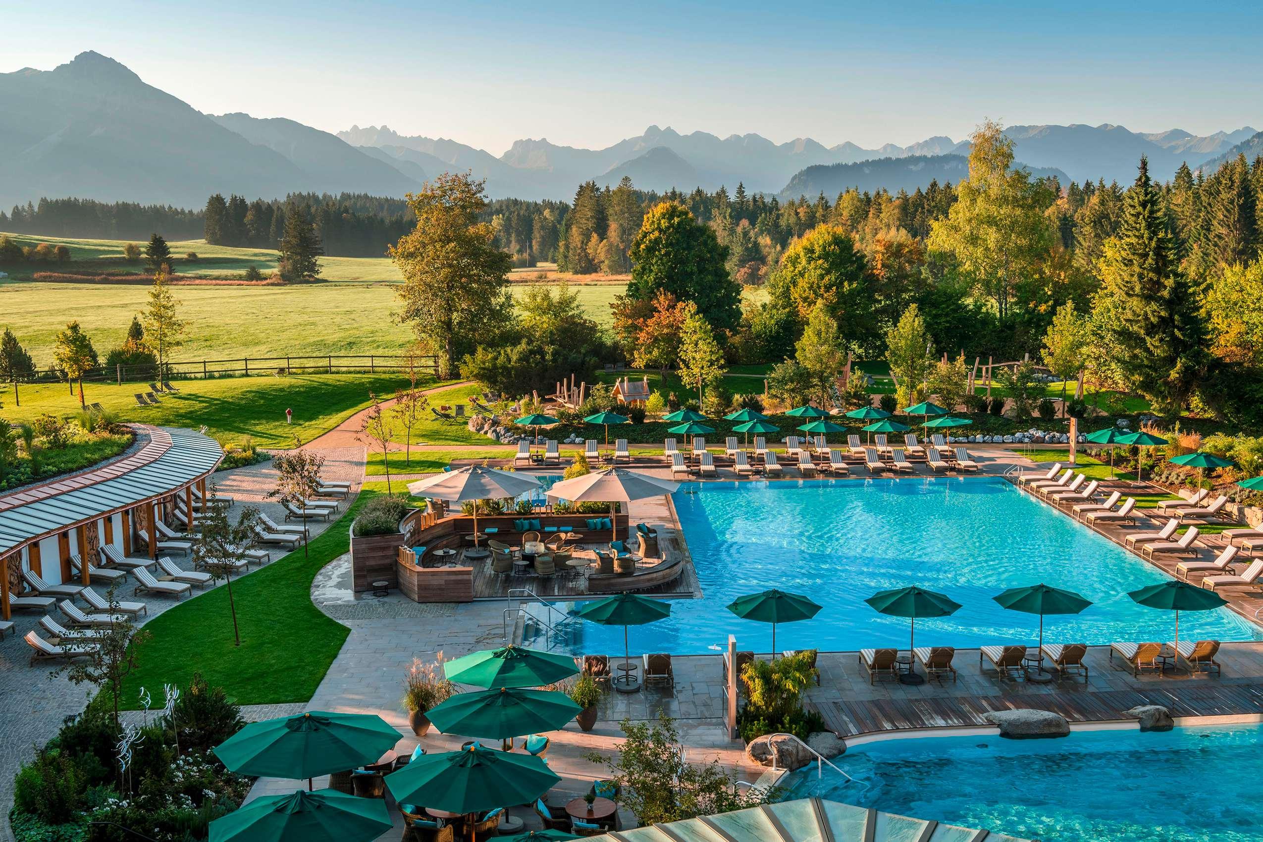 Die Poollandschaft des Sonnenalp Resorts mit Blick auf das alpine Umland.