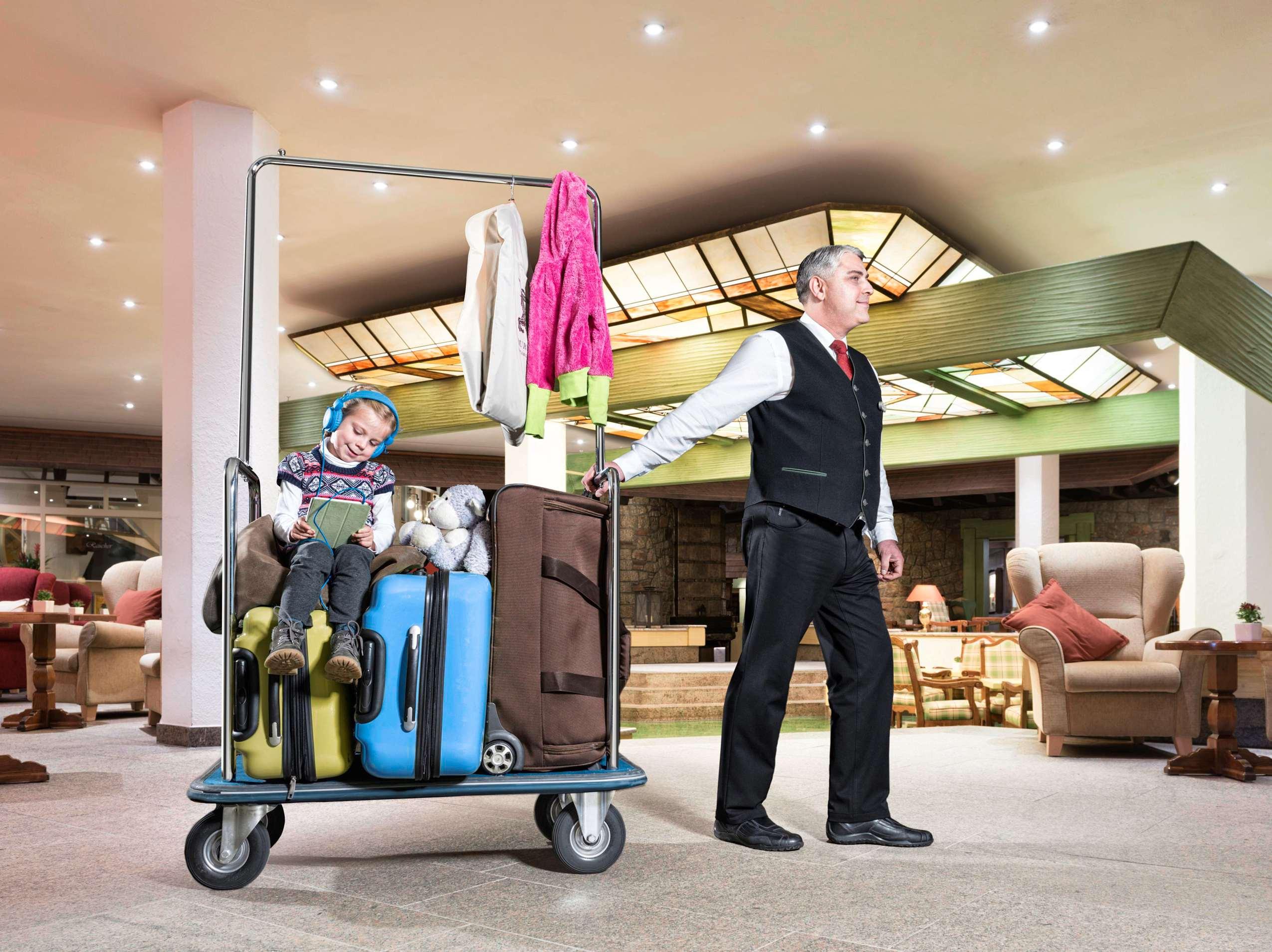 Page zieht Mädchen auf Kofferwagen durch die Lobby