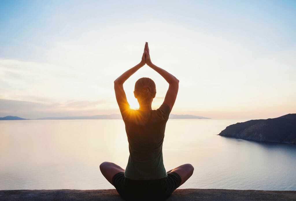 Junge Frau macht Yoga, im Hintergrund Bergpanorama und Sonnenuntergang