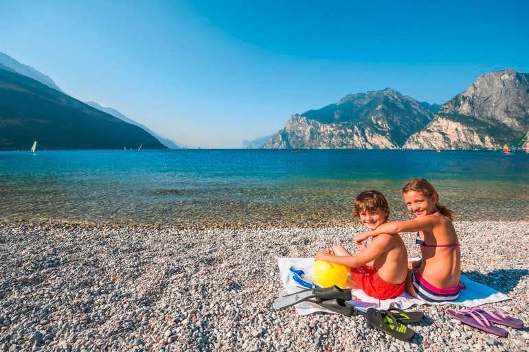 Gardaseeurlaub mit Kindern, die auf dem Kiesstrand am See sitzen.
