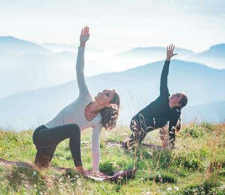 Zwei_Frauen_beim_Yoga_auf_der_Wiese_Wellnesshotels_Suedtirol